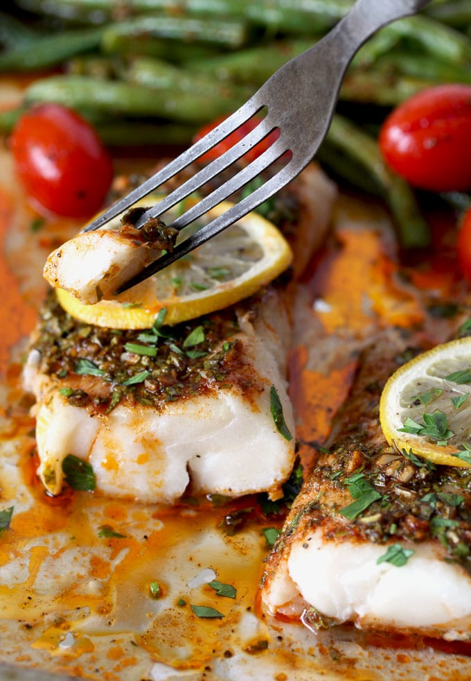 A fork picking up a piece of tender baked cod with chermoula sauce