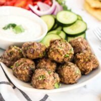 Juicy baked meatballs on a platter with Tzatziki sauce and cucumbers