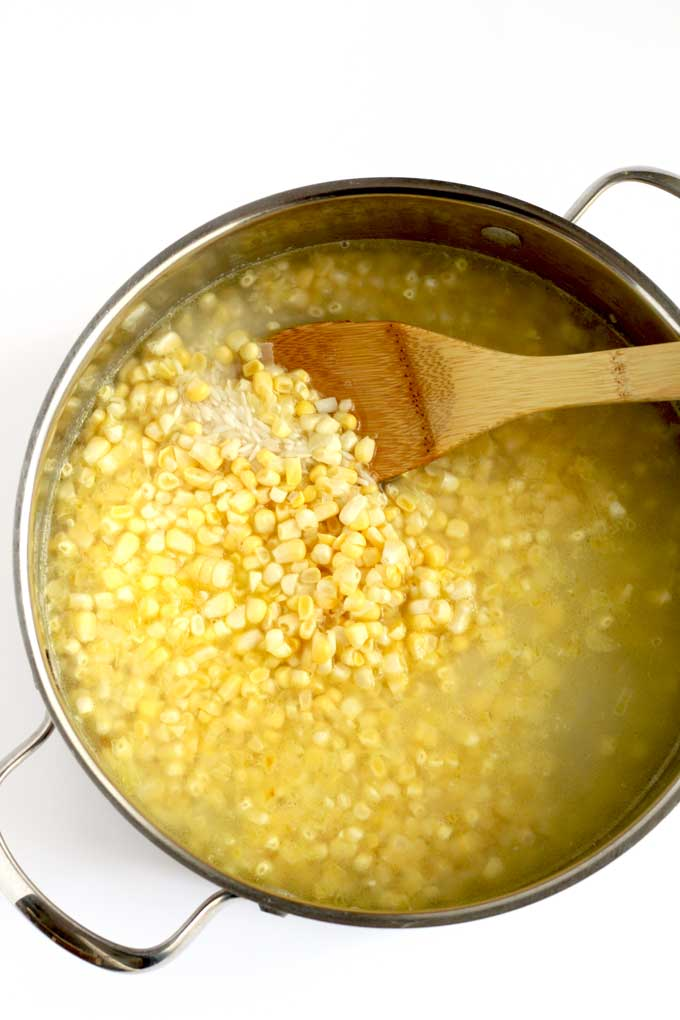 Sauteed onions, garlic, rice, corn and water in a pot.