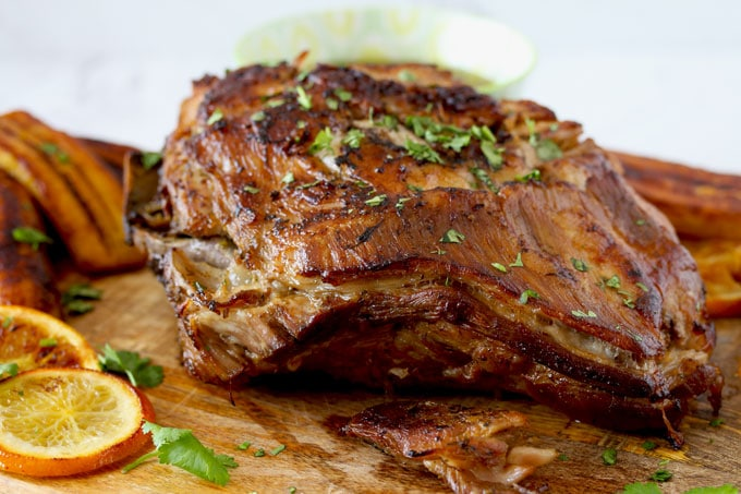 Easy and succulent Slow Cooker Cuban Mojo Pork perfectly golden sitting on a wooden board.