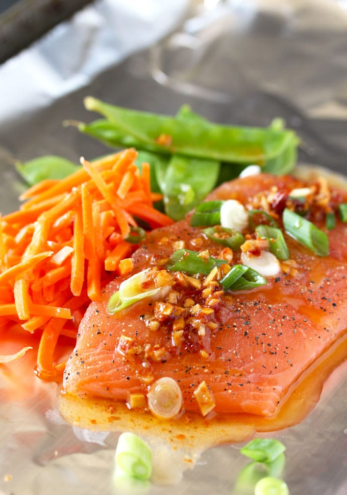 A piece of raw salmon drizzled with Asian Butter and topped with sliced green onions on a piece of foil. With shredded carrots and snow peas