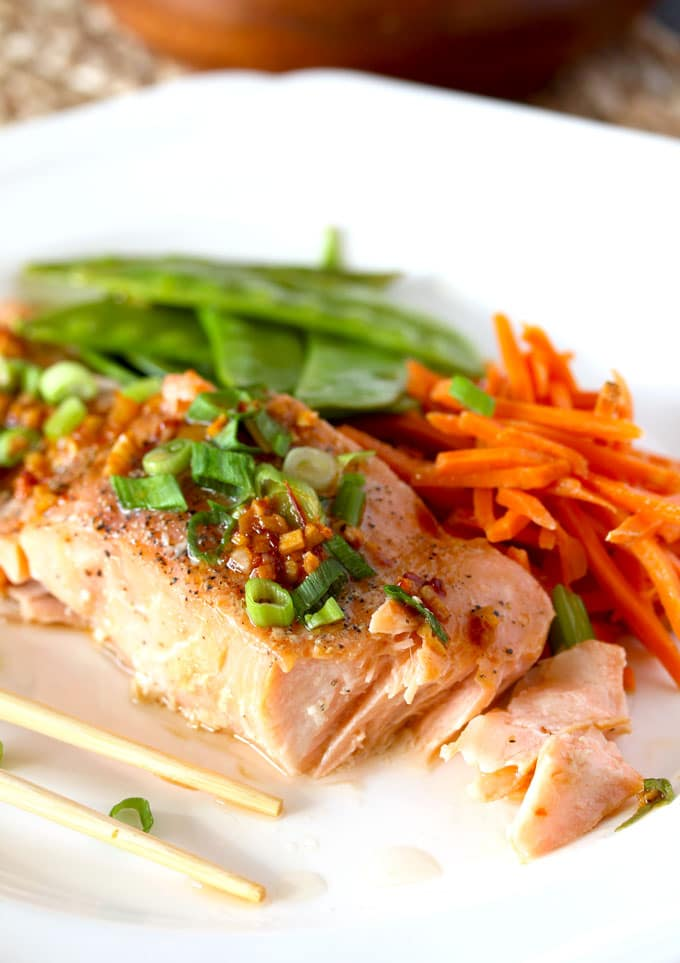 Asian Butter Salmon on a plate with chopsticks, Shredded carrots and snow peas