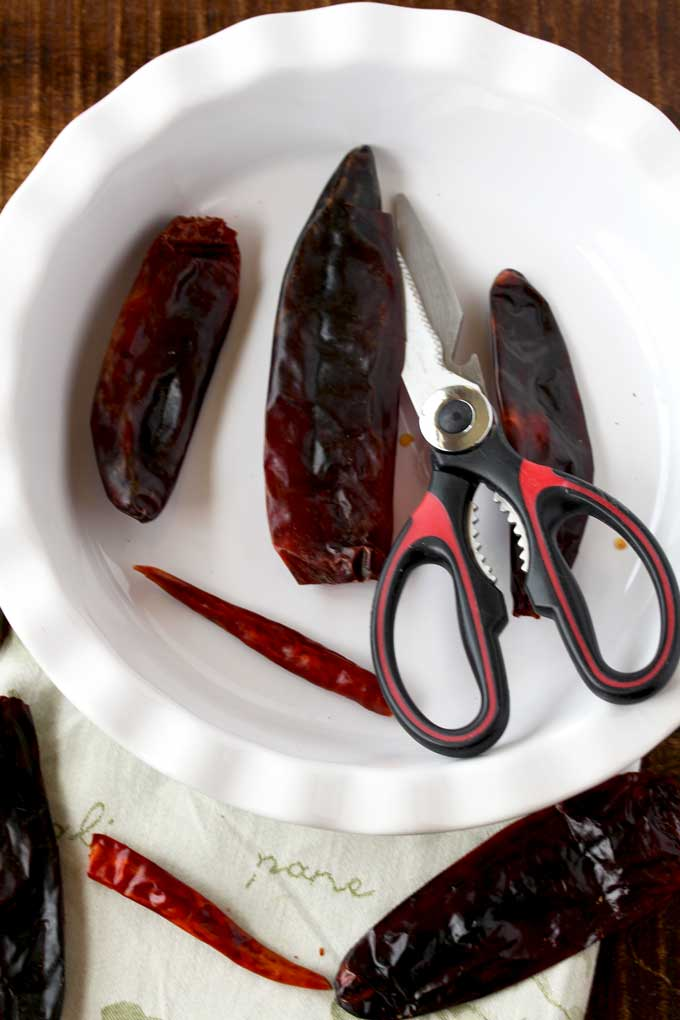 Pictured here dried chiles getting cut opened with kitchen shears