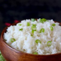 Light and fluffy cooked Jasmine with Gingered and Lemongrass in a wooden bowl garnished with thinly sliced green onions