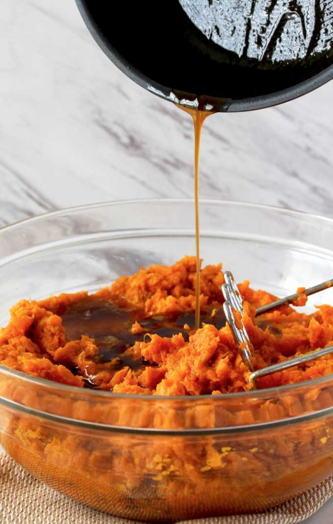 Close up view of a glass bowl filled with mashed sweet potatoes and a masher. Brown butter is pouring over the mashed sweet potatoes from a small pot.