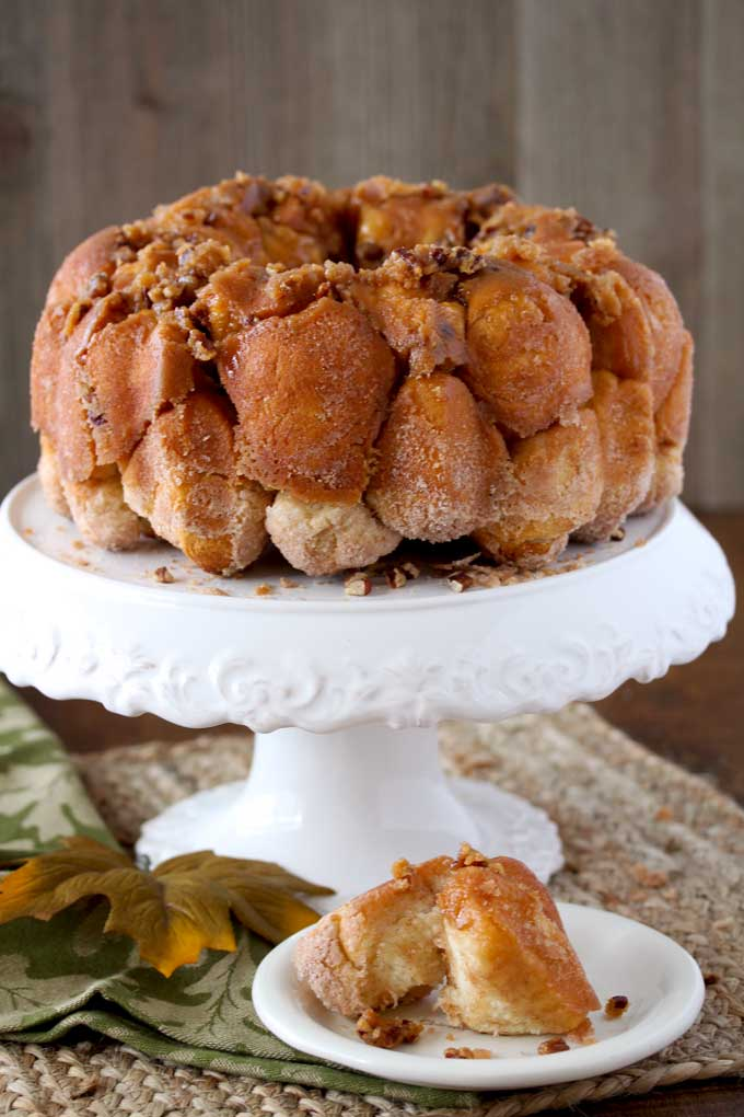 View of a monkey bread on a white pedestal cake stand sitting on a yute mat. Next to it is a small plate with two pieces of bread.