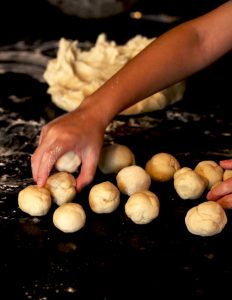 View of a child's hand rolling dough balls. On the black counter a big piece of dough and some small dough pieces rolled into small balls