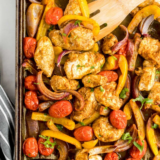 chicken, bell peppers and cherry tomatoes shawarma style on a sheet pan.