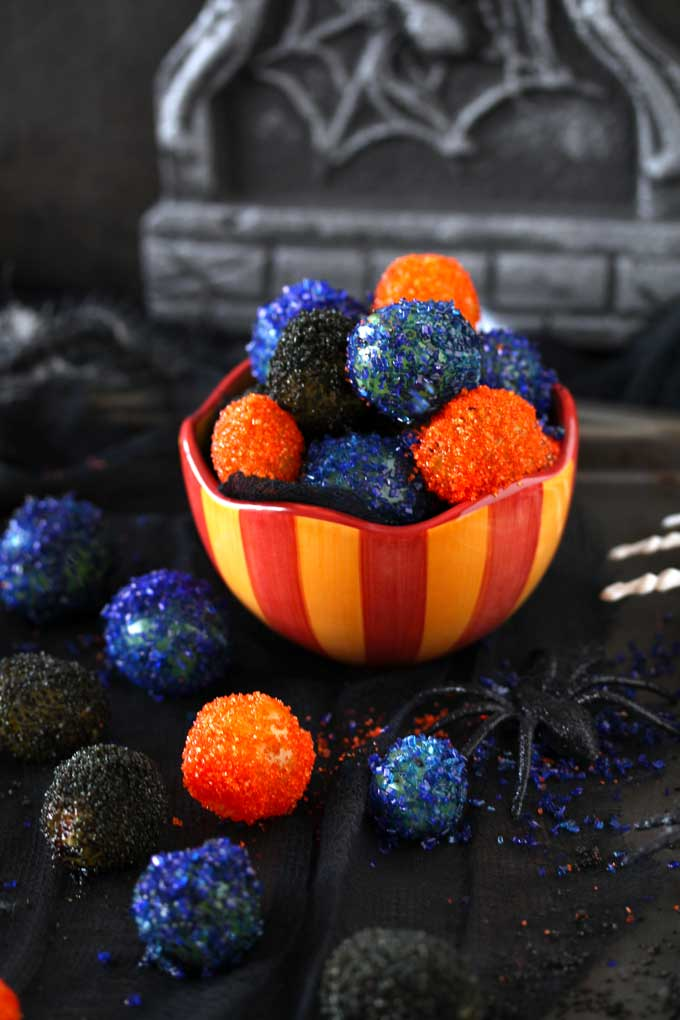 View of a candy bowl filled with sugared covered grapes. The sugared grapes are orange, purple and black. Sitting on a black cloth.