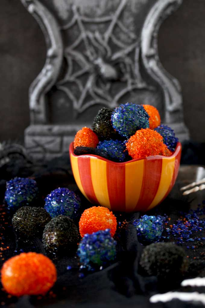 View of a candy bowl filled with sugared covered grapes. The sugared grapes are orange, purple and black. Sitting on a black clothes.