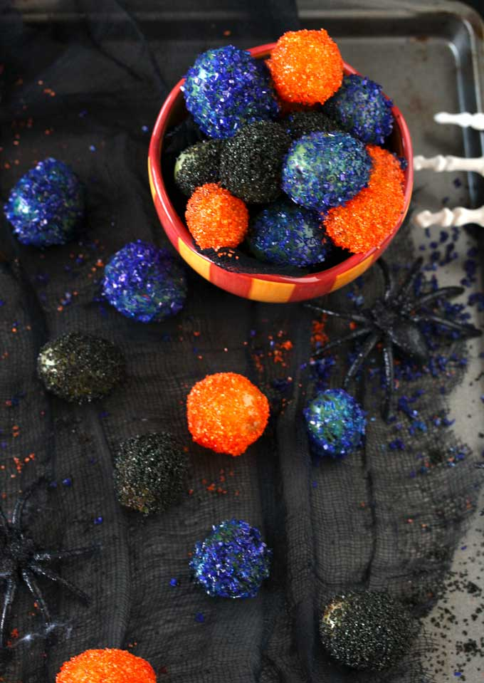 Overhead view of a candy bowl filled with sugared prosecco grapes in black, orange and purple over a black surface. There are a few fake spiders and a skeleton hand trying to reach the candy bowl.
