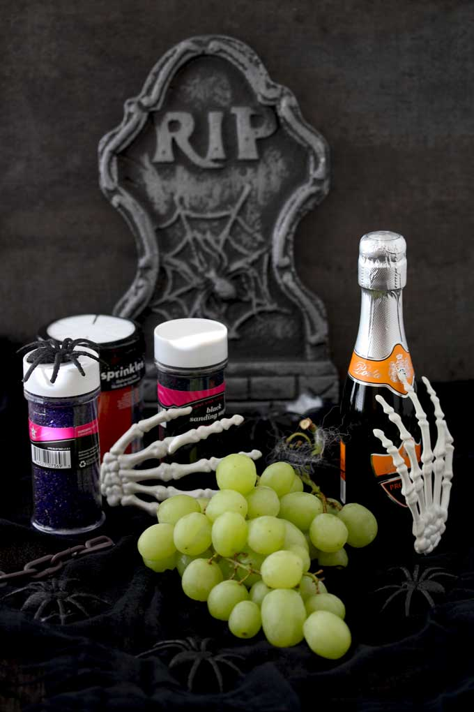 View of a cluster of green grapes, a bottle of Prosecco and colored sugars in black, oramge and purple. You can also see Halloween decorations such as spiders and skeleton hands sitting on a black surface.