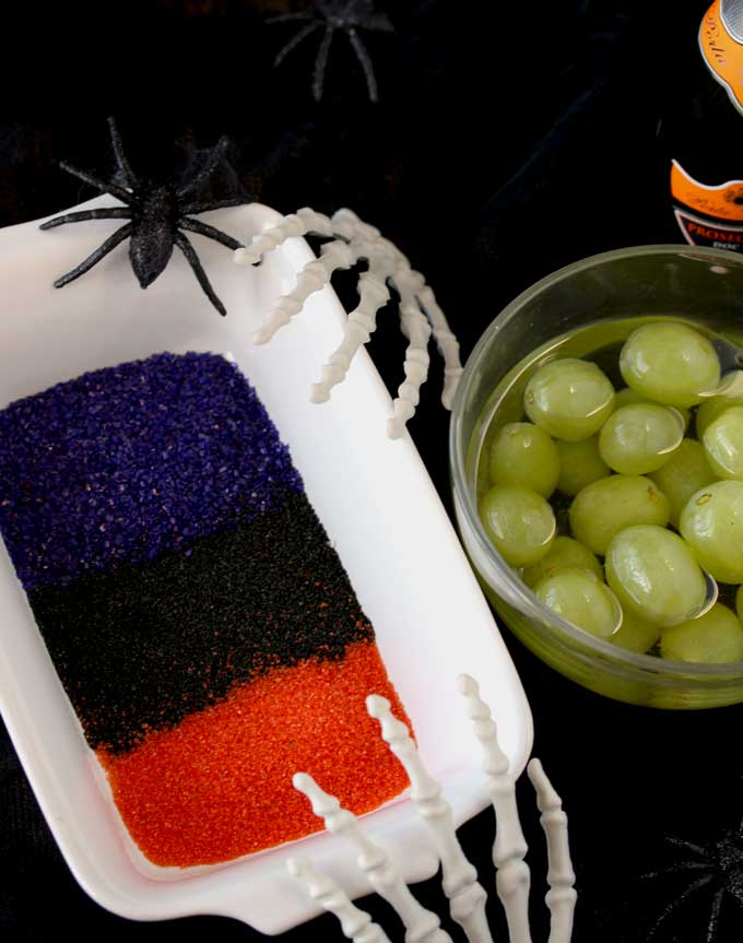 View of a small bowl filled with prosecco and grapes. and a plate showing orange, black and purple sugar.