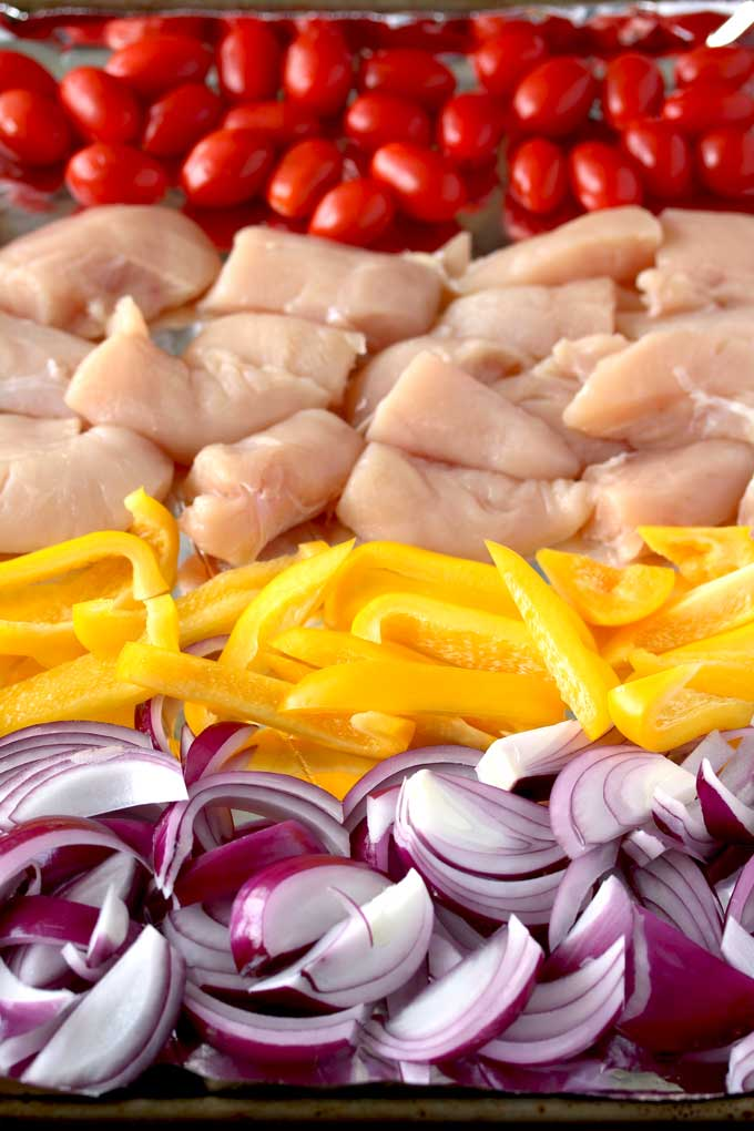 View of a sheet pan with rows of cherry tomatoes, chicken raw chicken pieces, sliced yellow bell peppers and sliced red onions.