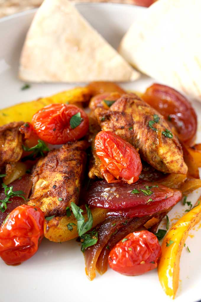 Close-up view of chicken tenders mixed with sliced yellow bell peppers, sliced red onions and cherry tomatoes served on a white plate and garnished with chopped parsley. Pita bread triangles set on one side of the plate.