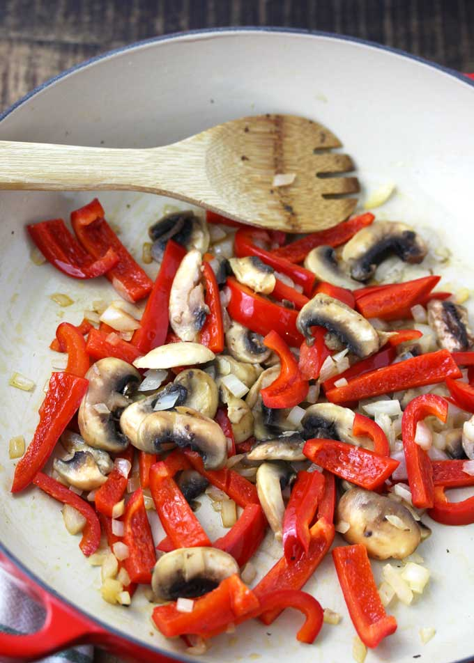 View of saute onions, red bell peppers and sliced mushrooms in a skillet.