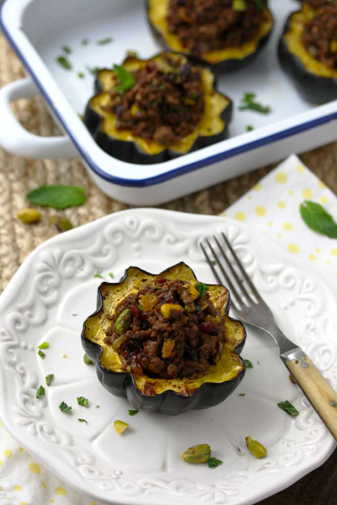 A stuffed acorn squash on a plate garnished with chopped herbs and pistachios. Also a white and blue baking dish filled with stuffed acorn squash on a wooden table