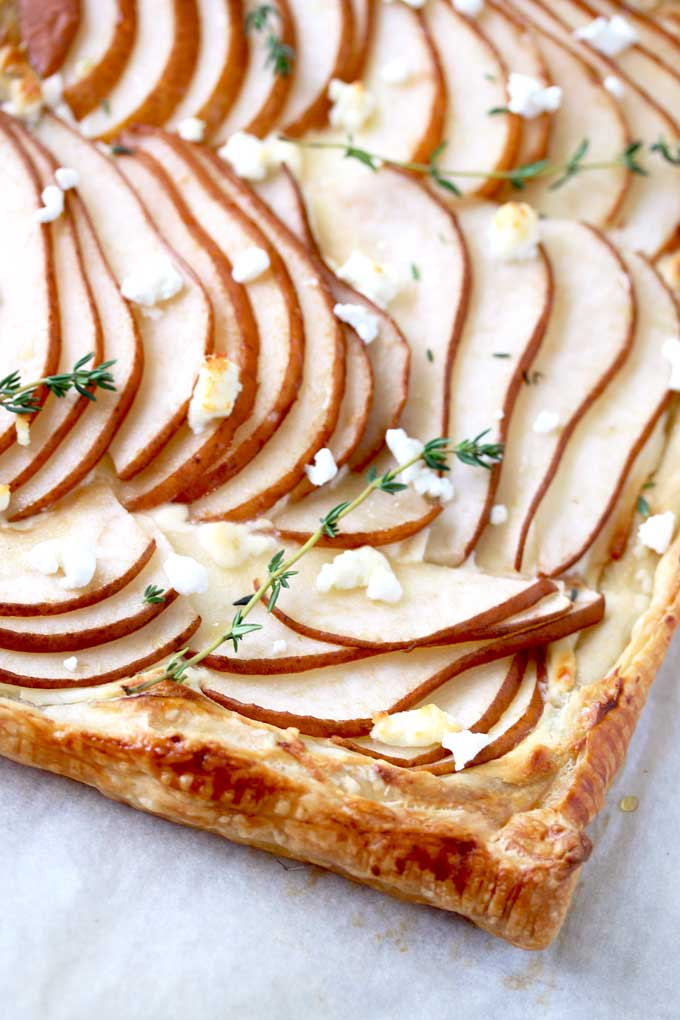 View of a golden brown puff pastry tart topped with thinly sliced pears garnished with goat cheese and fresh thyme on a parchment paper lined baking sheet.