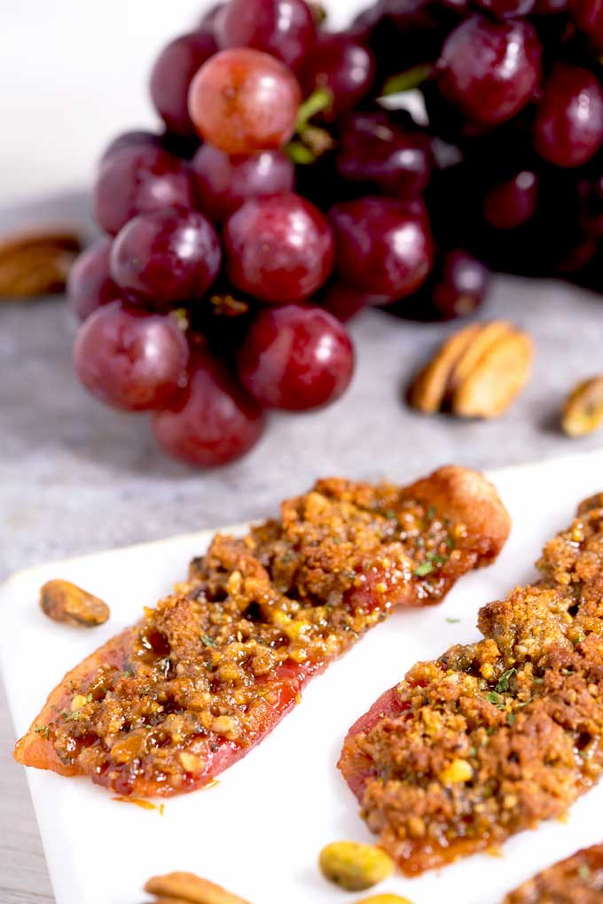 Slices of nutty caramelized bacon served on a white plate garnished with grapes.