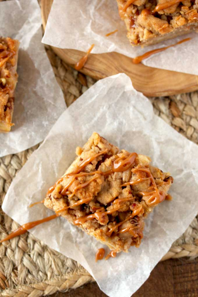 Over head view of a piece of apple pie bar on top of a square piece of parchment paper