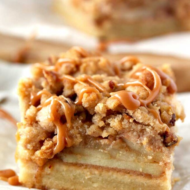 Close up side view of an apple pie bar with a pecan crumble and drizzled with salted caramel sitting on a piece of parchment paper over a rustic straw place mat. You can see the layers of shortbread crust at the bottom, a layer of apples in the middle and the crumbly top.