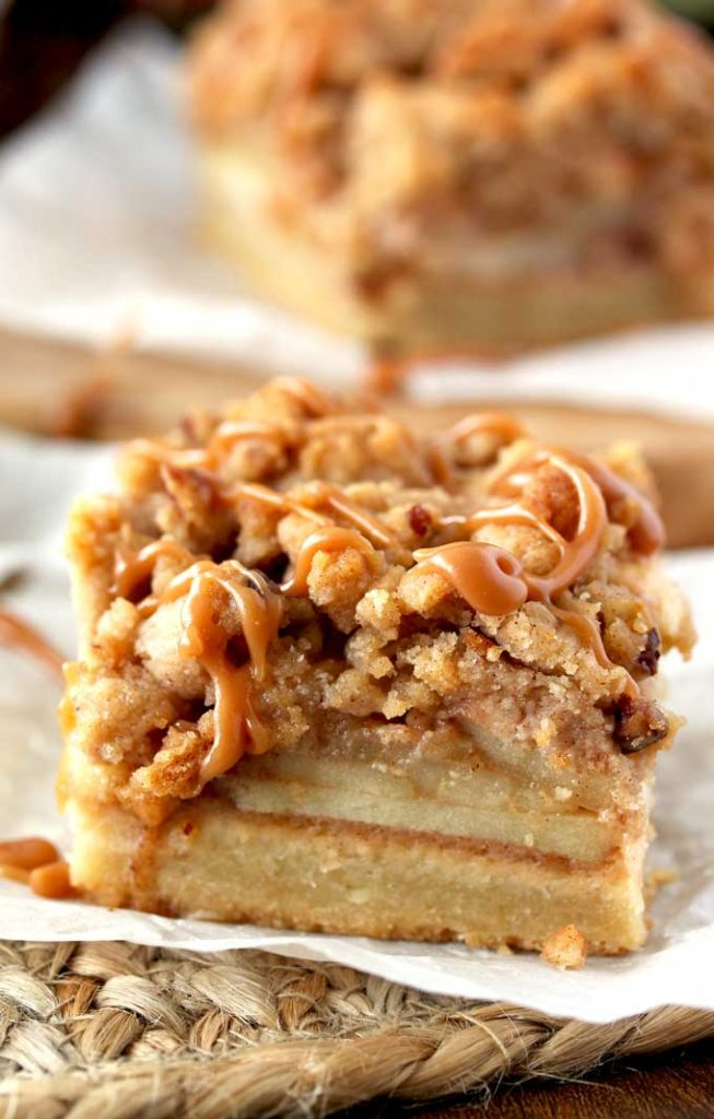 Close up side view of an apple pie bar with a pecan crumble and drizzled with salted caramel sitting on a piece of parchment paper over a rustic straw place mat. You can see the layers of shortbread crust at the bottom, a layer of apples in the middle and the crumbly top/