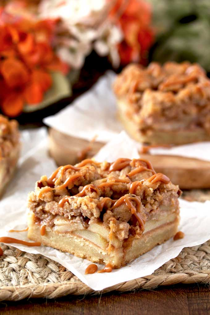 Side view of 3 apple pie bars with a pecan crumble and drizzled with salted caramel sitting on pieces of parchment paper on top of a rustic straw place mat. On the background a cluster of orange and cream hydrangeas.
