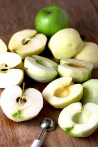 View of peeled and cored apples on a cutting board. Next to them you can see a melon baller.