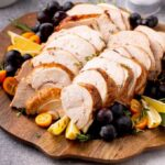Sliced turkey breast in a wooden tray garnished with herbs and fruits