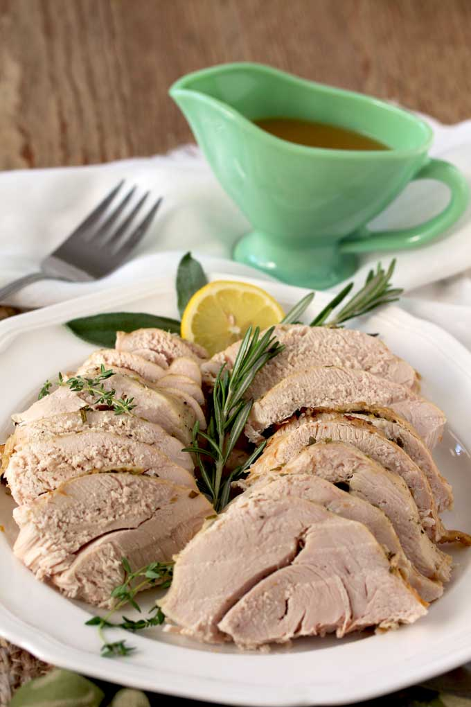 A platter with thin slices of turkey breast garnished with fresh rosemary, thyme, sage on a wooden surface. Next to the platter is a green gravy boat filled with gravy.