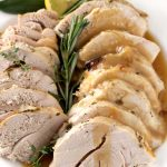 Close up view of a platter with slices of turkey, covered with gravy. Rosemary, thyme and a slice of lemon garnished the platter,
