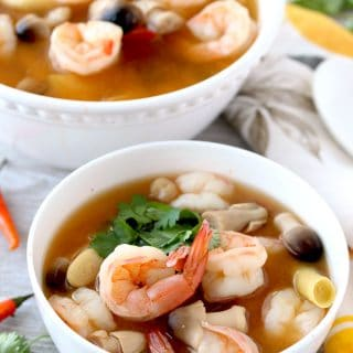 Two white bowls filled with Thai Tom Yum Soup. You can see plump cooked shrimp, straw mushrooms, lemongrass, fresh cilantro and red Thai chile peppers on a white wood board
