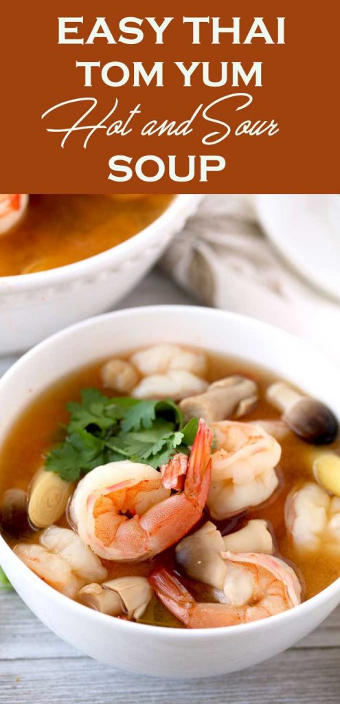 Close up view of a bowl of Thai Tom Yum Soup with plump shrimp, straw mushrooms, lemongrass and cilantro on a white wooden board
