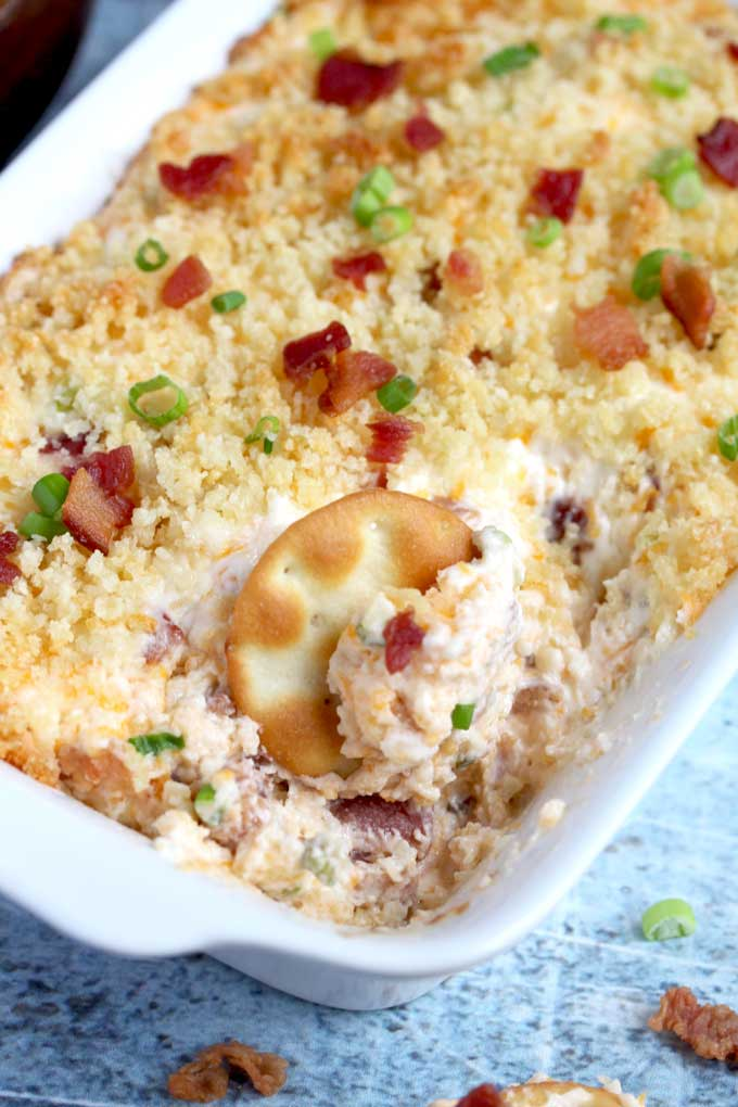 Close up view of bacon dip scooped with a cracker.