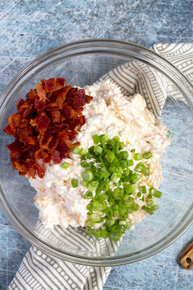 Dip mixture in a bowl topped with crispy bacon and green onions.