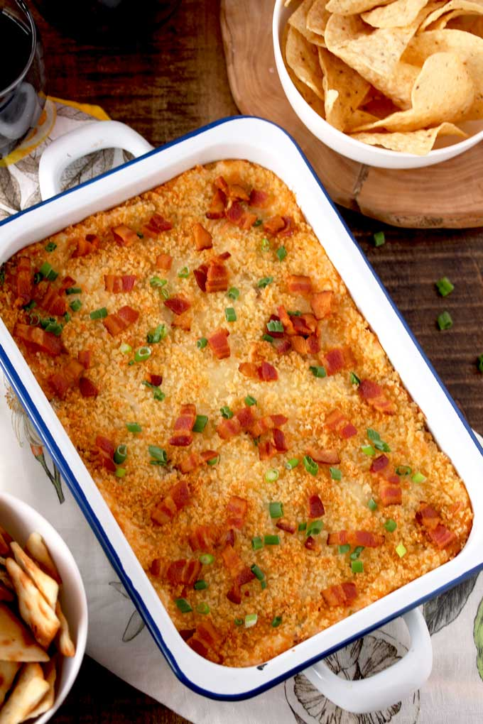 Top view of a white baking dish filled with hot and cheesy bacon dip with a crispy topping, garnished with crispy bacon and sliced green onions on a wooden board.