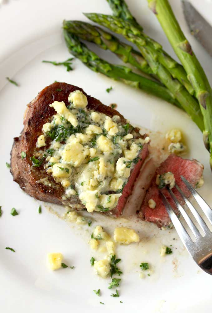 Top view of a white plate with pan seared filet mignon topped with blue cheese butter. On the plate a for is holding a thin slice of steak.