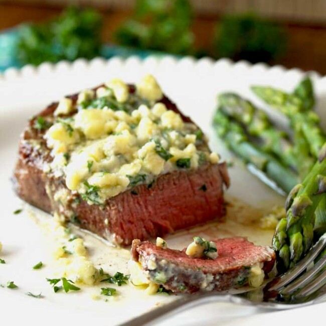 Close up view of a perfectly seared filet mignon topped with melty blue cheese butter. It has been sliced thinly and it is cooked to medium rare temperature. Also on the plate, sauteed asparagus.