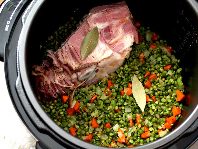 In this photo a pressure cooker (instant pot) filled with a mix of saute chopped onions, carrots, celery and minced garlic. With raw split peas. On one side there's a ham bone and bay leaves.