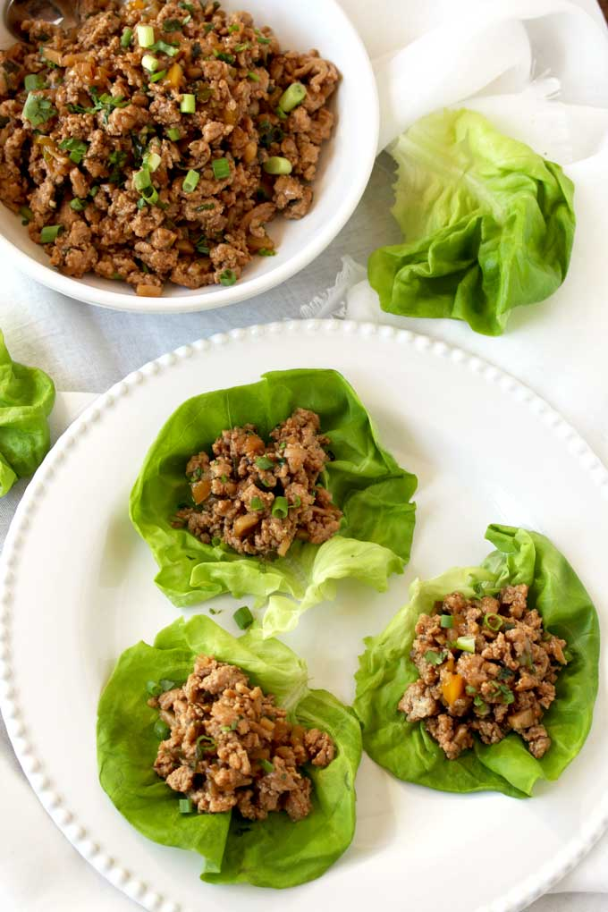 A white plate with chicken lettuce wraps next to a bowl filled with the Asian chicken filling.