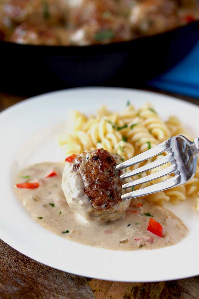 A Cajun Chicken meatball served with pasta on a white plate.