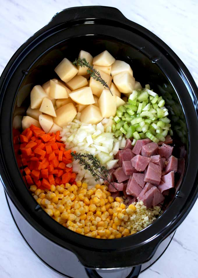 Pictured here is a slow cooker filled with cubed potatoes, chopped onions, celery, carrots, corn, minced garlic and thyme sprigs.