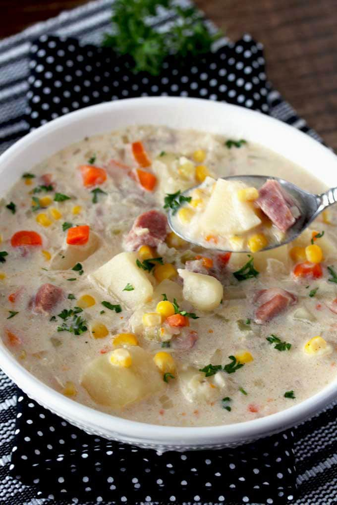 Pictured here a spoon scooping hearty and creamy potato and ham soup from a soup bowl.