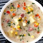 Top view of a white bowl filled with creamy ham and potato soup with potatoes, corn and carrots and garnished with chopped parsley sitting on a striped black and white table mat.