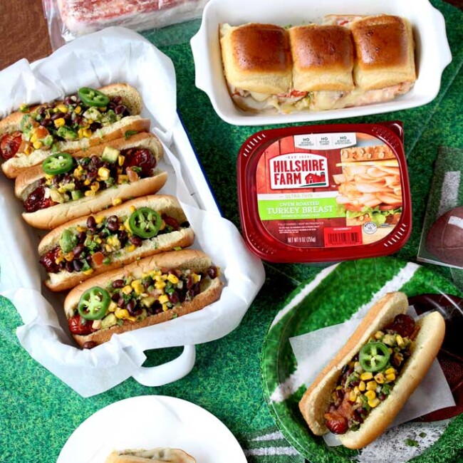 Game Day Foods set up over a green tablecloth. Southwest Bacon Wrapped Hot Dogs on a tray garnished with cilantro and jalapeno slices and pesto turkey sliders. Also a package of sliced turkey, hot dogs and bacon.
