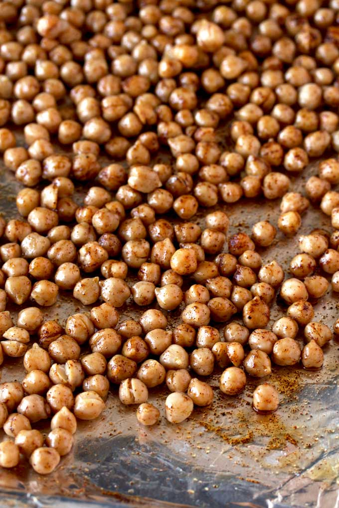 Seasoned chickpeas on a baking sheet ready to be roasted.