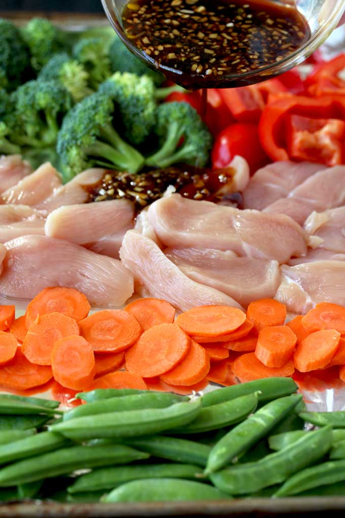 Pictured here a small bowl with stir fry sauce is been poured over a sheet pan with ingredients to make this easy Asian Chicken and Vegetables Stir Fry. Raw chicken, sliced carrots, red bell peppers, broccoli florets and sugar snap peas.