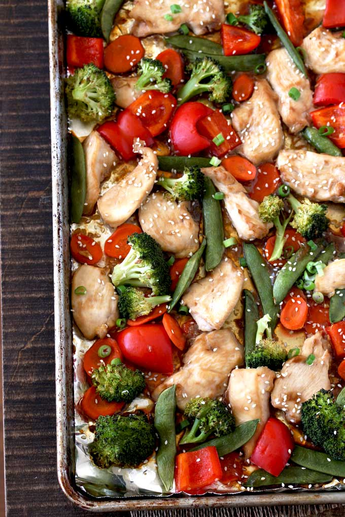 Pictured here a sheet pan with Asian Chicken Stir Fry and vegetables, broccoli florets, red bell peppers, sliced carrots and sugar snap peas.