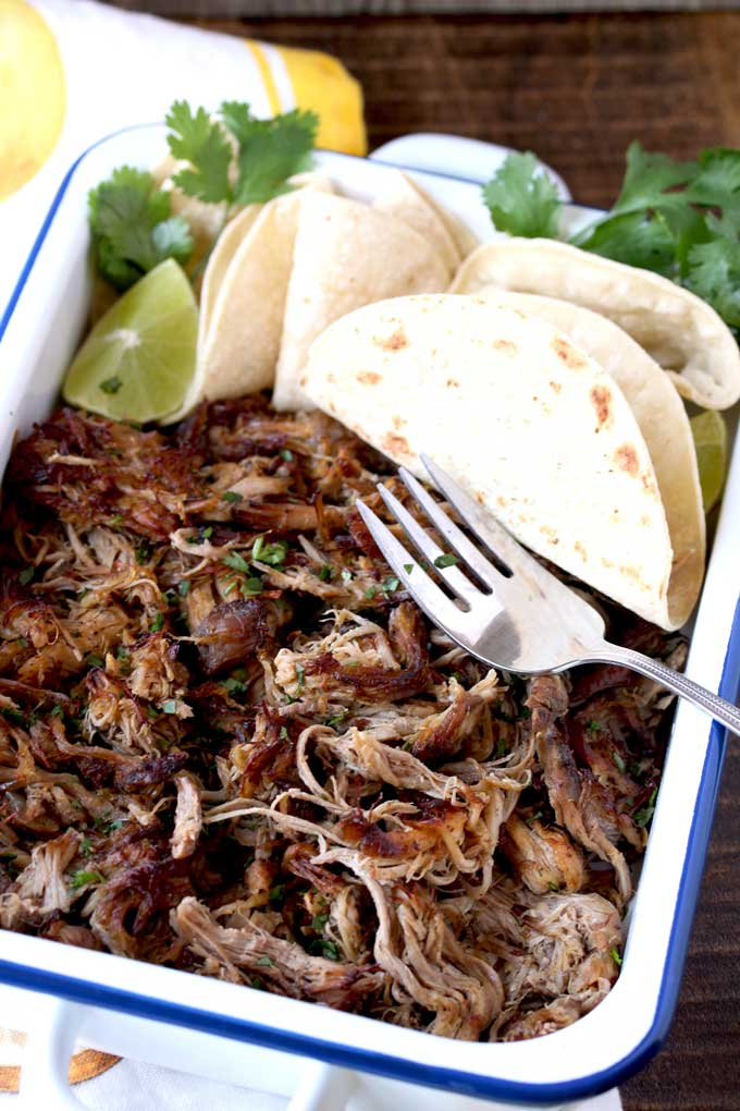 Pictured here a white serving dish filled with shredded slow cooker carnitas, flour tortillas, lime slices and garnished with chopped cilantro.