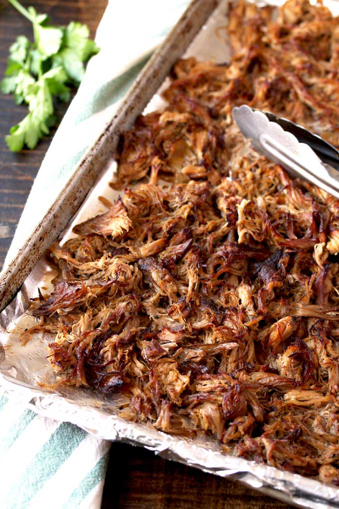 View of a sheet pan containing tender shredded slow cooker carnitas,